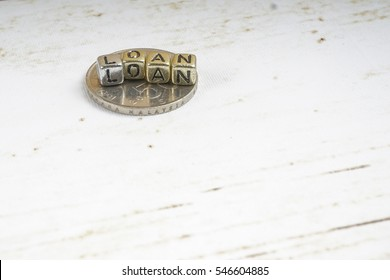 LOAN word with coins on rustic background. Business concept. Shallow DOF