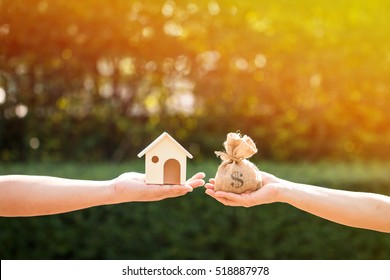 Loans for real estate concept, a man and a women hand holding a money bag and  a model home put together in the public park.