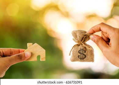 Loans for real estate concept, a women hand holding a money bag and a home model together in the public park.