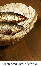 Loaves of bread and two fishes in a basket