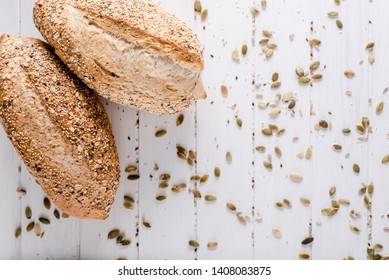 Loaves of freshly baked bread with a scattering of grain on a white wooden surface.Top view.