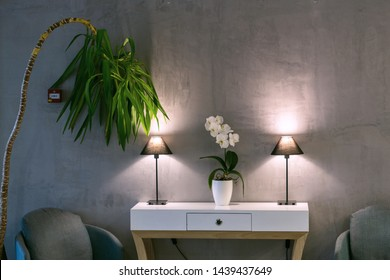Lobby with dimmed lights on a desk with comfortable chairs and a palm tree