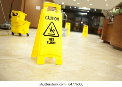 "Lobby floor with mop bucket and ""caution wet floor"" signs, selective focus on nearest sign"