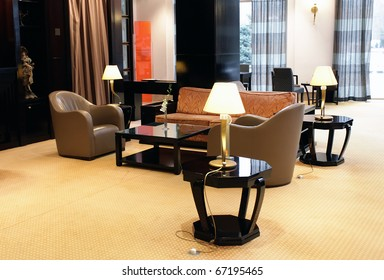 Lobby interior of a hotel with sofa and armchairs surrounded by lamps