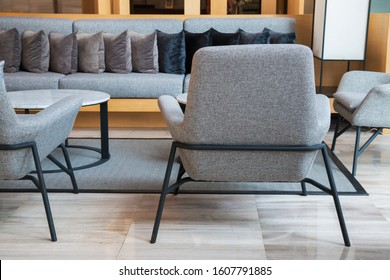 Lobby lounge with grey long sofa, armchairs and round tables on grey carpet in modern residential building.