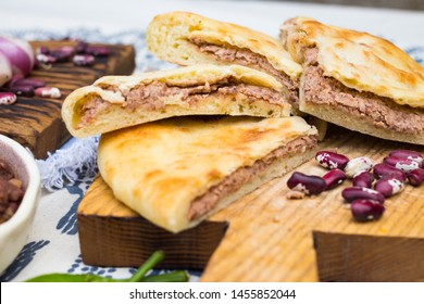 Lobiani pie - Georgian cuisine traditional food stuffed with red kidney or white beans (lobio) inside on wooden board and Lurji Supra tablecloth.