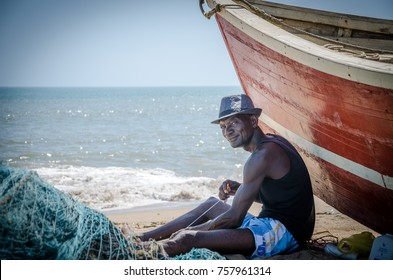 LOBITO, ANGOLA - MAY 09 2014: Unidentified Angolan fisherman sitting in front of red fishing boat at beach fixing nets