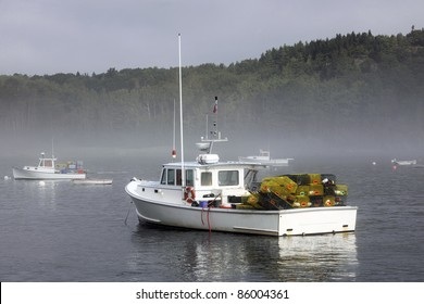 A lobster boat loaded with trips in a harbor with other boats where a morning mist remains.