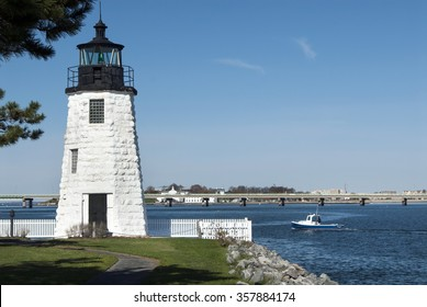 Lobster boat passes by Newport Harbor lighthouse in Rhode Island. The stone tower is one of many Newport attractions.