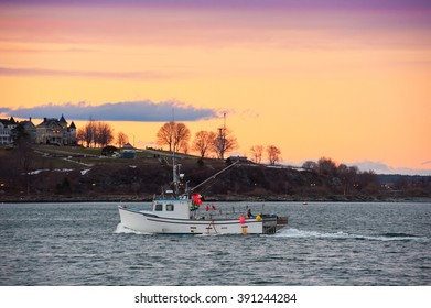 Lobster boat returns to Portland, Maine harbor at sunset