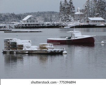 Lobster boat and traps in quiet, snowy harbor
