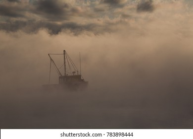 Lobster boats in Maine in the sea smoke at sunrise