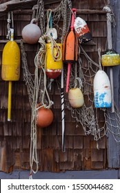 Lobster buoys with fishing nets on a wooden barn wall, New England coast