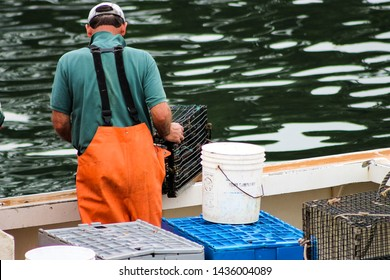 Lobster fisherman pulling a lobster trap into his boat.