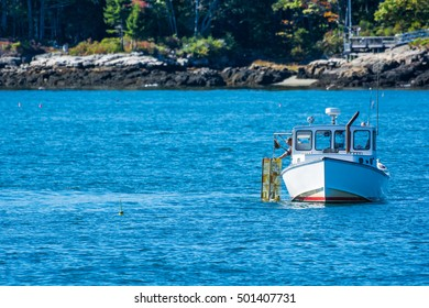Lobster fishing boat in autumn against deep blue ocean water in coastal Maine, New England
