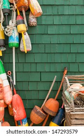 Lobster fishing buoys and traps against a deep green wood shingled wall. Colorful image with copy space