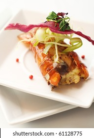 Lobster with melted cheese, topped with vegetable, place on white plates with white background.