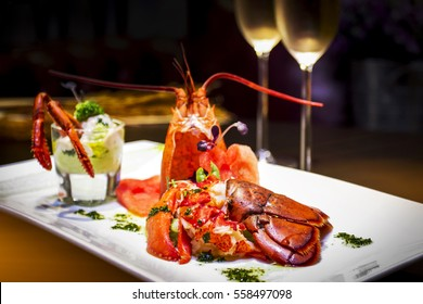 The lobster on the white square plate serve with two glasses of wine.