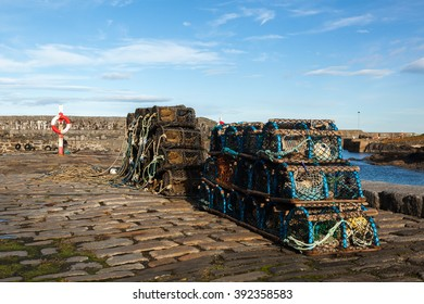 Lobster pots or creels drying in the sun at Portsoy Harbour, Aberdeenshire, Scotland UK.