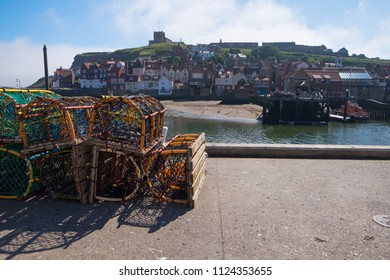 Lobster pots on Whitby pier with harbour and town in background