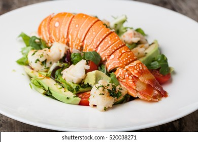 lobster with salad on a white plate