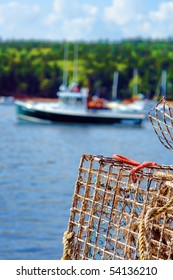 Lobster trap on a dock in a Maine coastal port with blurry fishing boat sailing by in the water
