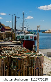 Lobster traps and fishing boats at the wharf in Peggy's Cove, Nova Scotia, Canada.
