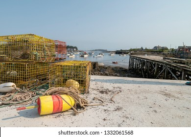 Lobster traps sit next to harbor at low tide. There is a floater attached by a rope. The floaters are color coded so the lobster fisherman can identify their traps in the ocean.