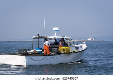 Lobstermen haul traps on a summer day in Maine with lighthouse in the distance. Lobstering is a seacoast tradition.