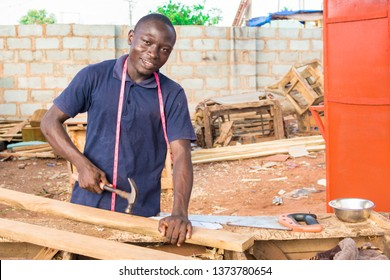 local african carpenter at work smiling