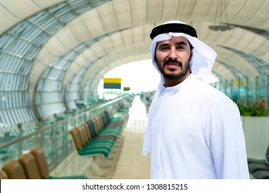 Local Arab man inside airport wearing traditional UAE means wear white kaffiyeh kandora.