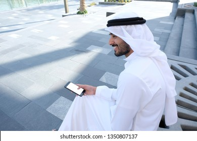 Local Arabic Middle Eastern Man smiling while holding a smart mobile phone mock up