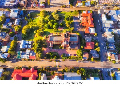 Local architectural historic landmark in modern city Newcastle of Australia. Aerial overhead view down to Cathedral site, roof and local park surrounded by residential houses and streets.