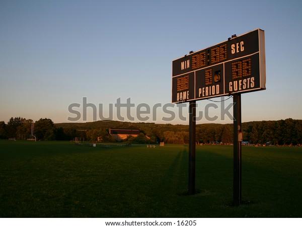 A local baseball scoreboard in some pretty light.