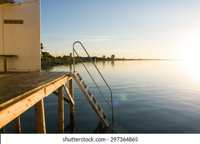 The local bathing pier with clear water beneath it. A small sandy beach in the background. Its sunrise
