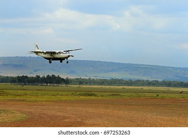 A local biplane landing on a dirt strip in the African Bush.  Flying into the bush is popular because of the long distances and bumpy roads.  Masai Mara, Kenya 2011