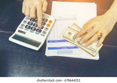 Local businessman using calculator figuring out total price of merchandises , paid by US dollar bills