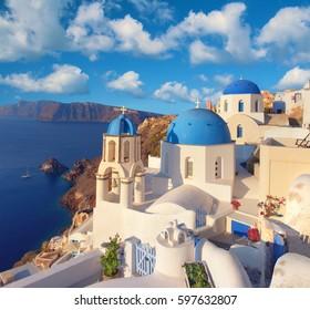 Local church with blue cupola in Oia village, Santorini island, Greece. Panoramic image.