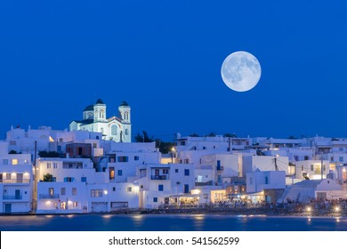 Local church of Naoussa village at Paros island in Greece against the full moon.