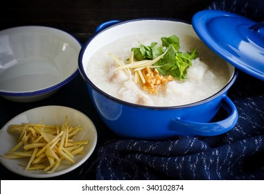 Local cuisine of Asia  : porridge rice gruel with fish served in blue bowl, congee. Still life image dark tone.