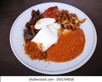 """Local dish named """"lontong darat"""" very Delicious Lontong Darat - Malaysian and Indonesian Traditional Food in a white plate on the table."""