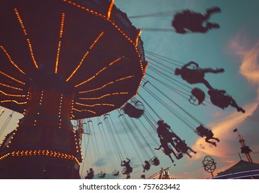 a local fair at dusk with people riding swinging rides and enjoying the summer atmosphere toned with a retro vintage instagram filter app or action