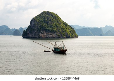 A local fisherman boat among the karst formations in Halong Bay, Vietnam, in the gulf of Tonkin. Halong Bay is a UNESCO World Heritage Site and the most popular tourist spot in Vietnam