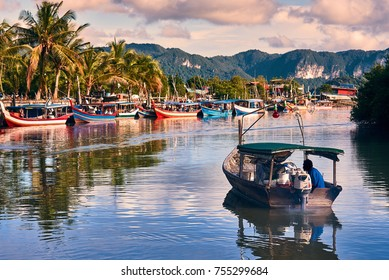 A local fisherman goes out on a boat from boats park to the sea for fishing. Traditional colorful asian fishing boats in fishing village. Langkawi island, Malaysia.