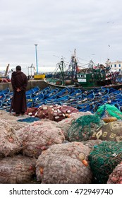 Local fisherman looks at the unloading of fish at the seaport in Essaouira, Morocco