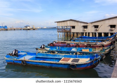 Local fisherman Wooden sampan boat anchored to the pier in the Chew Jetty in Penang, Malaysia