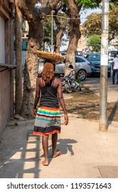 Local girl walking in Luanda Angola city view, slums and high-rise buildings in capital city of Angola. Luanda expensive city in West-Africa.