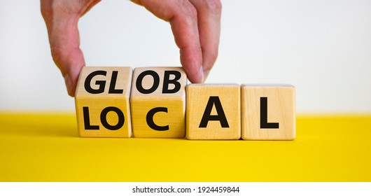 Local or global symbol. Businessman turns wooden cubes and changes the word 'local' to 'global'. Beautiful yellow table, white background. Business and local or global concept. Copy space.