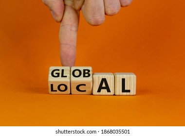 Local or global symbol. Hand turns cubes and changes the word 'local' to 'global'. Beautiful orange background. Business and local or global concept. Copy space.