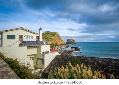Local houses, ocean view with dramatic sky and old fortress ruins on the steep rock. Typical Madeira island landscape in Porto da Cruz.